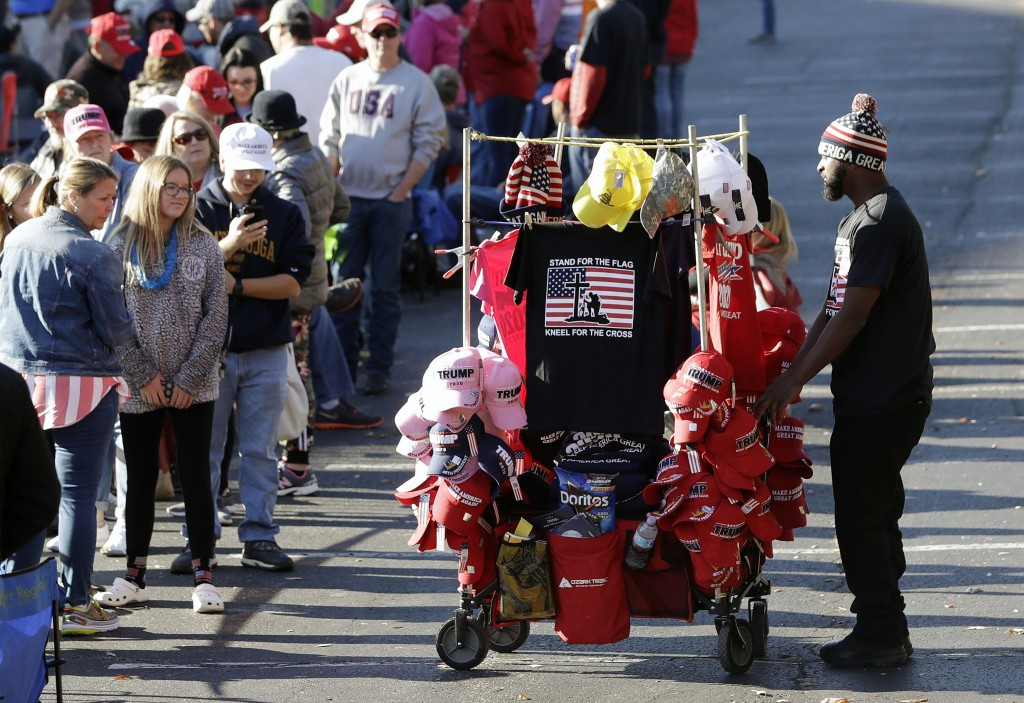 A vendor sells items to people waiting outside McKenzie Arena for a campaign rally by President Donald Trump Sunday, Nov. 4, 2018, in Chattanooga, Ten...