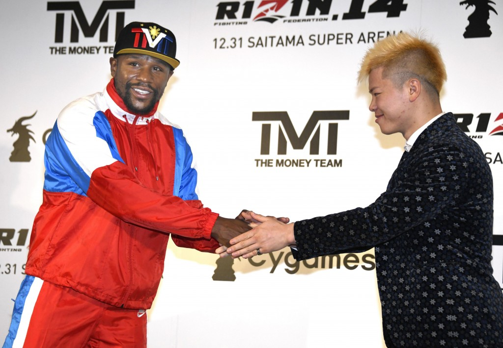 Floyd Mayweather, left, of the U.S. shakes hands with Japanese kickboxer Tenshin Nasukawa during a press conference in Tokyo, Monday, Nov. 5, 2018. Ma