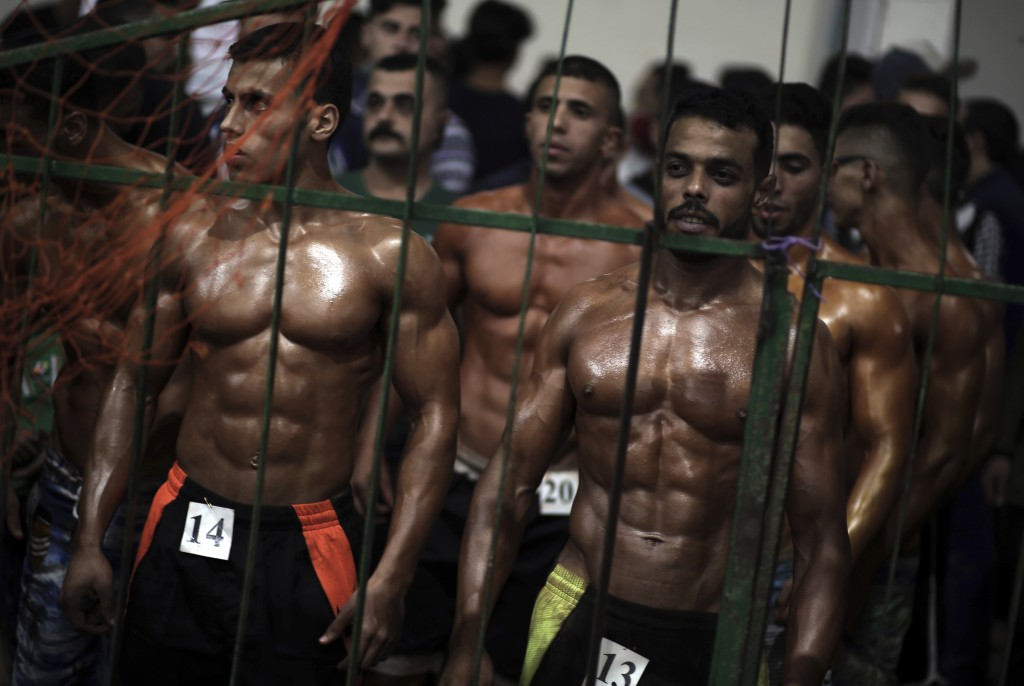 In this Friday, Oct. 26, 2018 photo, Palestinian contestants wait to perform on stage during a local bodybuilding competition, in Gaza City. Glistenin...