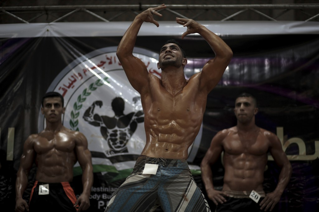 In this Friday, Oct. 26, 2018 photo, Palestinian contestants, including Abdallah al-Hour, 20, center, perform on stage during a local bodybuilding com...