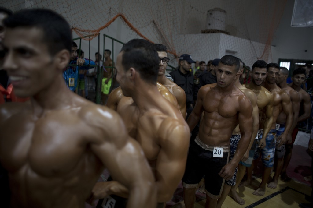 In this Friday, Oct. 26, 2018 photo, Palestinian contestants line up to perform on stage during a local bodybuilding competition, in Gaza City. Gaza's...