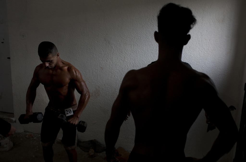 In this Friday, Oct. 26, 2018 photo, Palestinian contestants prepare themselves before  a local bodybuilding competition, in Gaza City. Gaza's 2 milli...