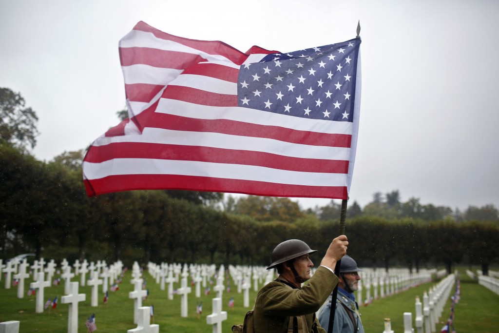 FILE In this Sunday, Sept. 23, 2018 file photo, re-enactors in World War I military uniforms carry an American flag in the Meuse-Argonne cemetery, nor