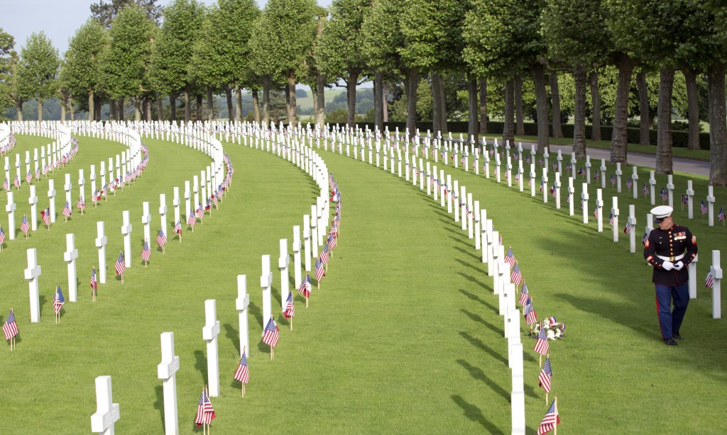 FILE  - In this Sunday, May 27, 2018 a US Marine walks among graves at the Aisne-Marne American Cemetery in Belleau, France.  After the United States