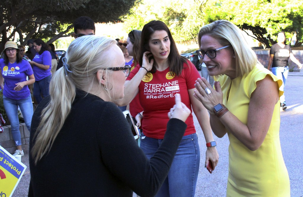 FILE--In this Nov. 3, 2018, file photo, a supporter, left, crosses her fingers as she talks with Democratic U.S. Senate candidate Kyrsten Sinema, righ...