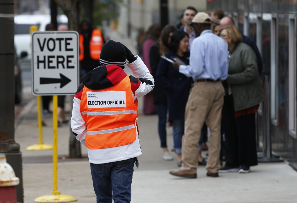 An election official, left, maintains the crowd line and parking spaces as people line up to vote at the Minneapolis Early Vote Center on the last day