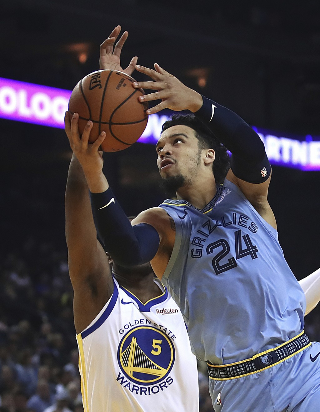 Memphis Grizzlies' Dillon Brooks, right, lays up a shot past Golden State Warriors' Kevon Looney (5) during the first half of an NBA basketball game M...