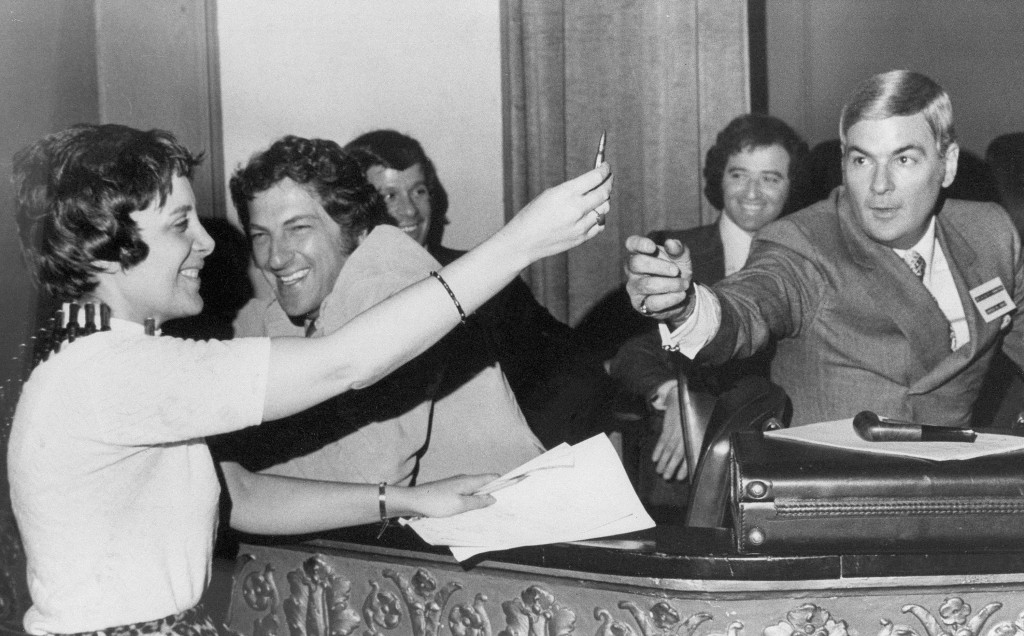 FILE- In this May 18, 1971, file photo Evelyn Y. Davis offers up a bullet from an ammunition bandolier, which she wore at the Wilmington, Del., stockh
