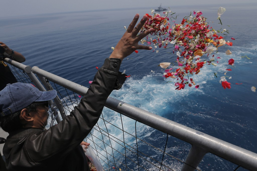 In this Tuesday, Nov. 6, 2018, file photo, a relative sprinkles flowers for the victims of the crashed Lion Air flight 610 from an Indonesia Navy ship