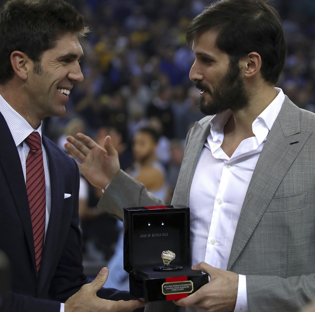 Golden State Warriors general manager Bob Myers, left, presents Memphis Grizzlies' Omri Casspi with his NBA championship ring prior to a basketball ga...