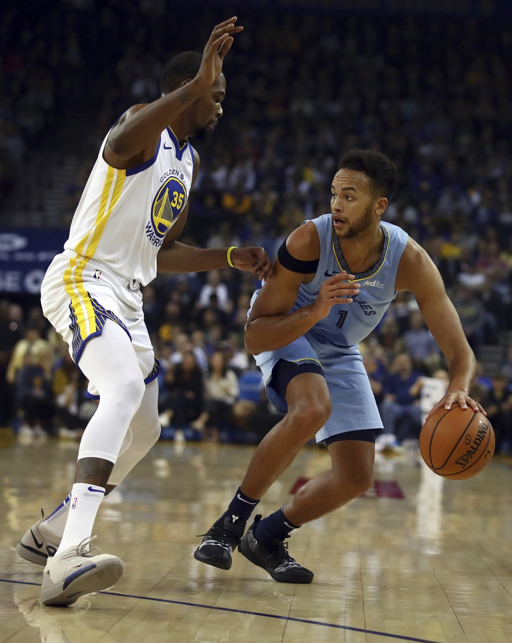 Memphis Grizzlies' Kyle Anderson, right, drives the ball against Golden State Warriors' Kevin Durant (35) during the first half of an NBA basketball g...
