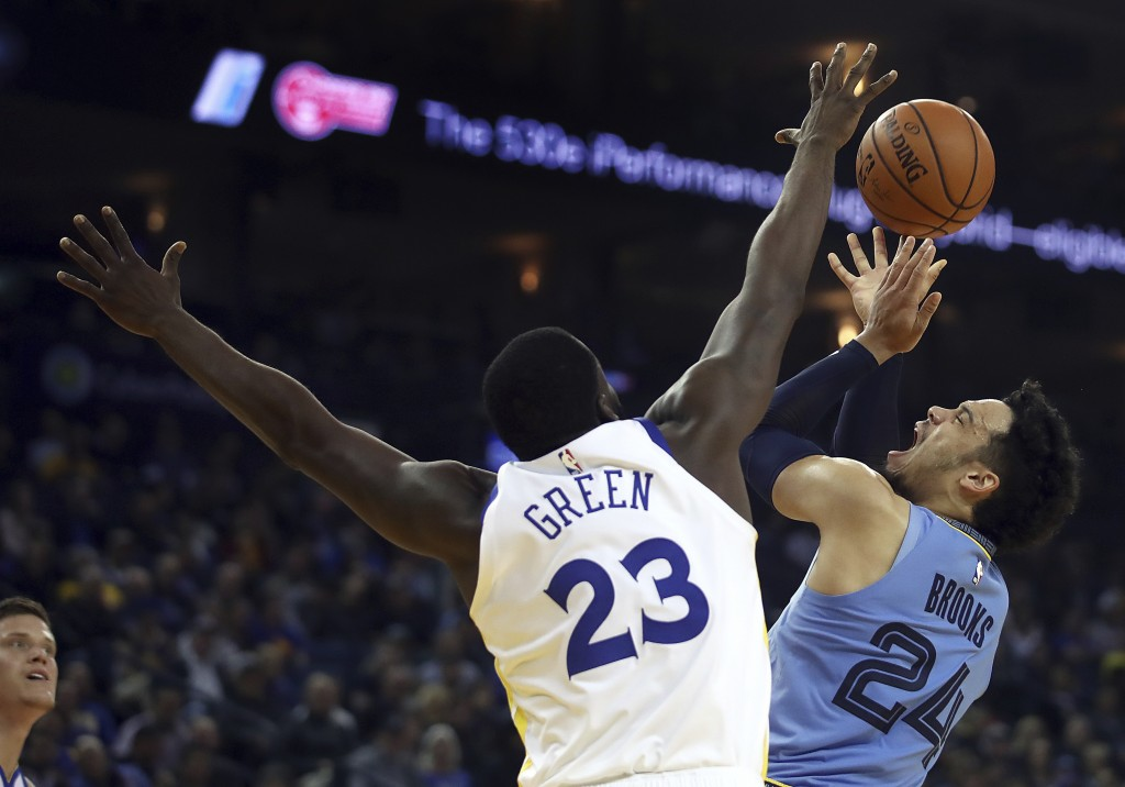 Memphis Grizzlies' Dillon Brooks, right, shoots against Golden State Warriors' Draymond Green (23) during the first half of an NBA basketball game Mon