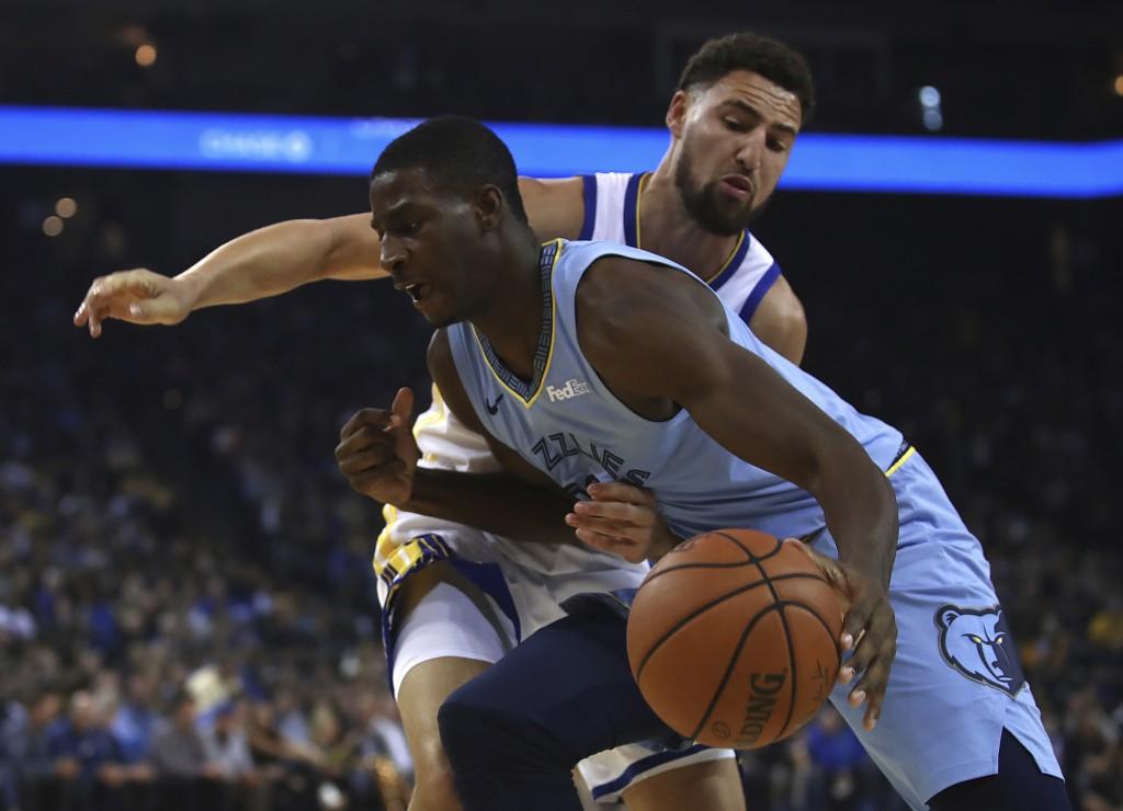 Memphis Grizzlies' Jaren Jackson Jr., left, drives the ball against Golden State Warriors' Klay Thompson during the first half of an NBA basketball ga...