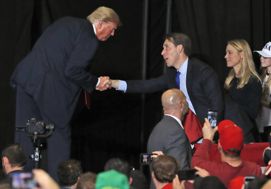 President Donald Trump shakes hands with Republican Senate candidate Josh Hawley, center, while walking off stage at the end of a campaign rally as Ha