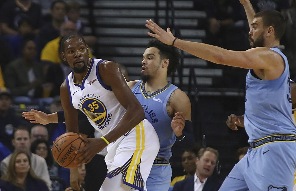 Golden State Warriors' Kevin Durant, left, looks to pass away from Memphis Grizzlies' Dillon Brooks, center, and Marc Gasol, right, during the first h...