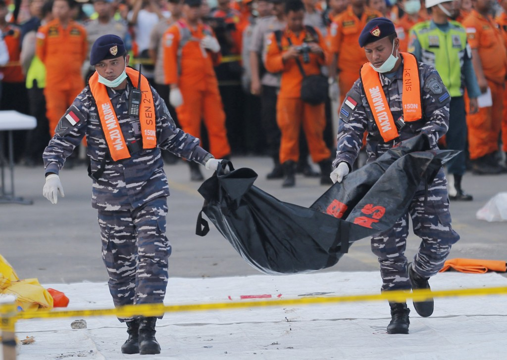 FILE - In this Thursday, Nov. 1, 2018, file photo, navy personnel carry the remains of a victim of Lion Air jet that crashed into the sea at the Tanju