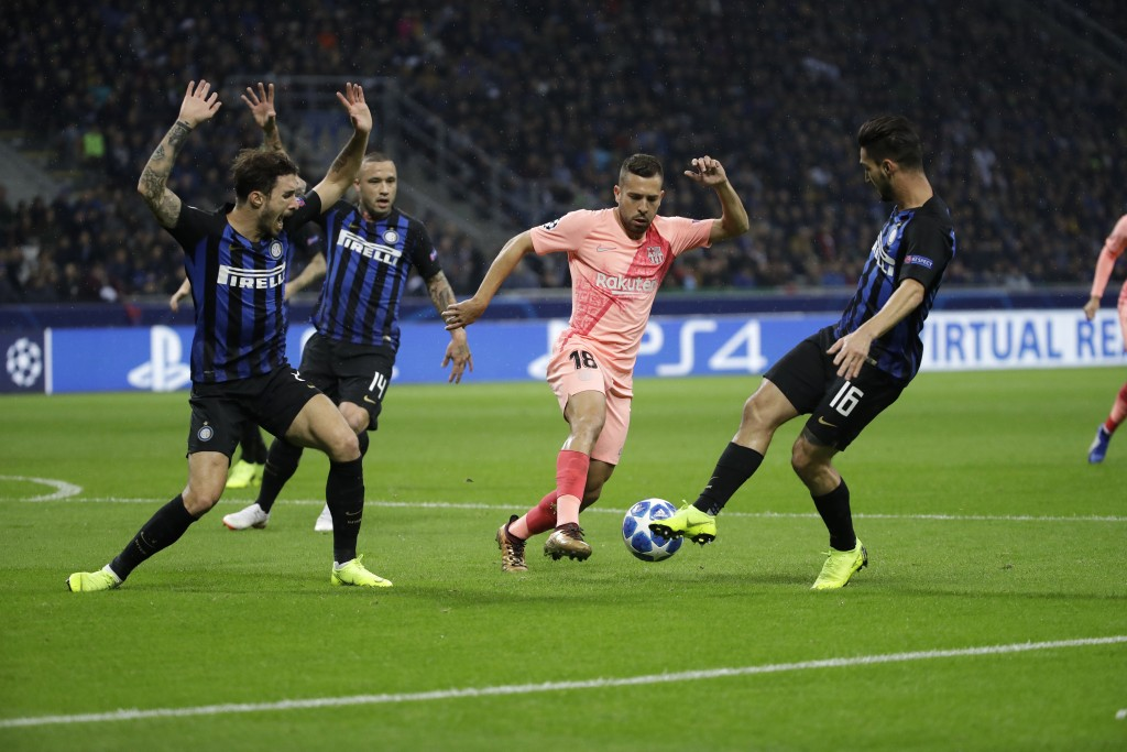 Barcelona defender Jordi Alba, second right, fights for the ball against Inter midfielder Matteo Politano, right, during the Champions League group B