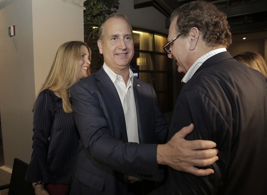 Congressman Mario Diaz-Balart, center, is greeted by his brother Lincoln Diaz-Balart as his wife, Tia, left, also greets supporters during a victory p...
