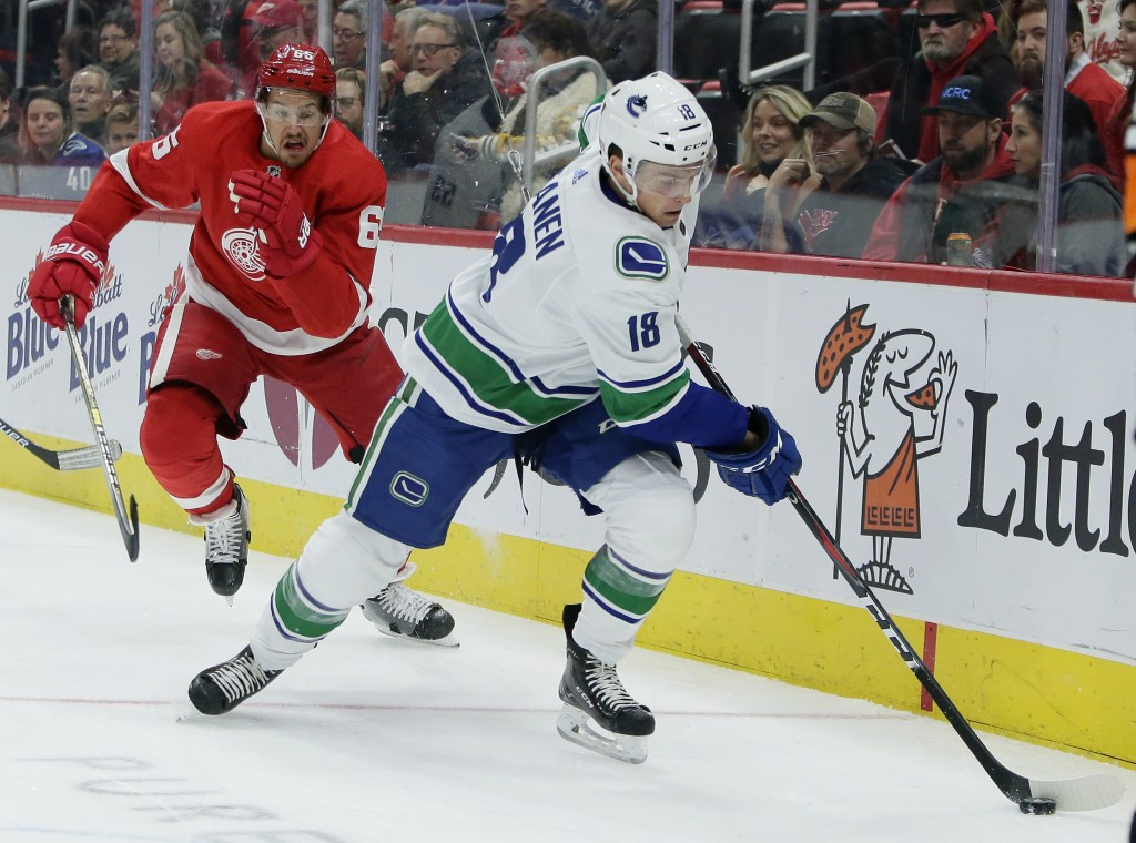 Detroit Red Wings defenseman Danny DeKeyser (65) pursues Vancouver Canucks right wing Jake Virtanen (18) behind the net during the first period of an ...