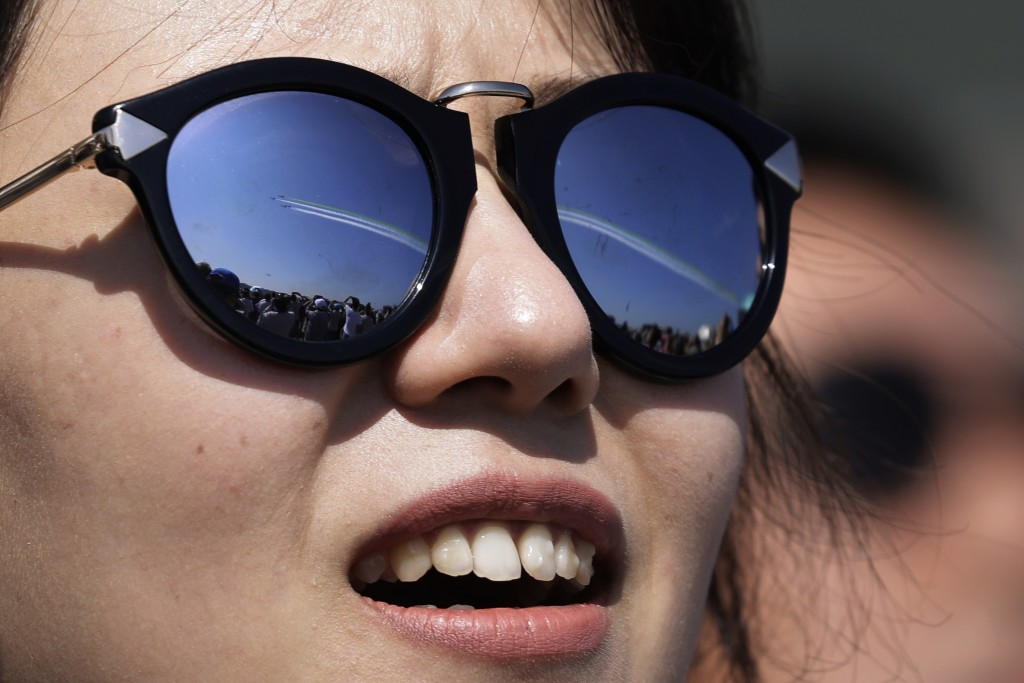 "In this Wednesday, Nov. 7, 2018, file photo, a visitor wearing sunglasses with the reflection of the China's K-8 aircrafts from the Aerobatic Team ""Ho"