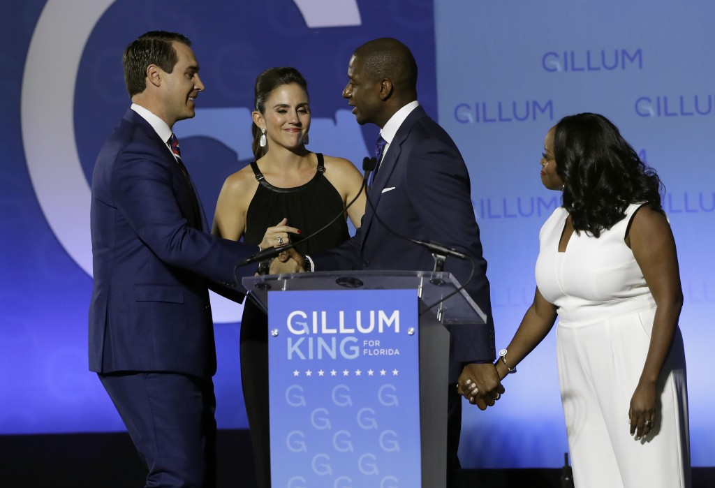 Florida Democratic gubernatorial candidate Andrew Gillum, second from right, shakes hands with running mate Chris King, left, as their wives Kristen K...