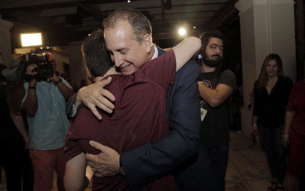 Congressman Mario Diaz-Balart hugs his son Cristian during a victory party at the Flamingo Terrace at Hialeah Park, Tuesday, Nov. 6, 2018, in Hialeah,...