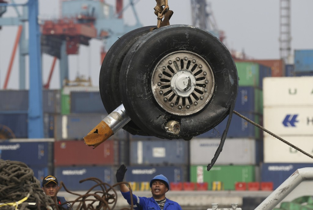 FILE - In this Saturday, Nov. 3, 2018, file photo, a crane moves a pair of wheels recovered from the Lion Air jet that crashed into the Java Sea for f