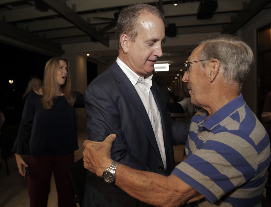 Congressman Mario Diaz-Balart, center, is greeted by a supporter during a victory party at the Flamingo Terrace at Hialeah Park, Tuesday, Nov. 6, 2018...