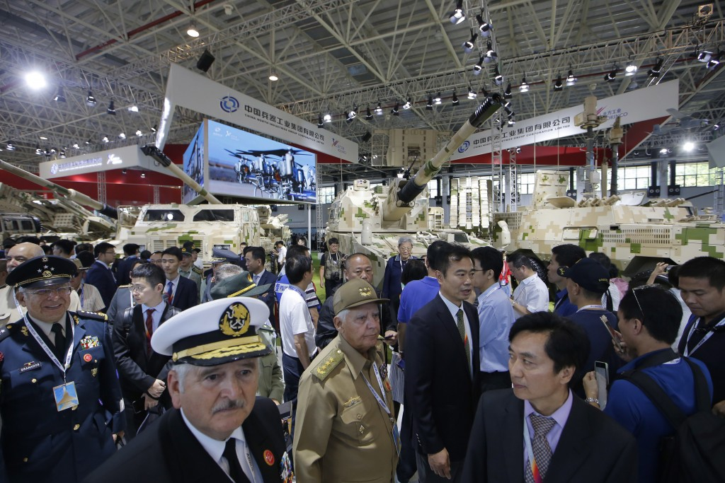 Visitors look at the military vehicles during the 12th China International Aviation and Aerospace Exhibition, also known as Airshow China 2018, Tuesda...