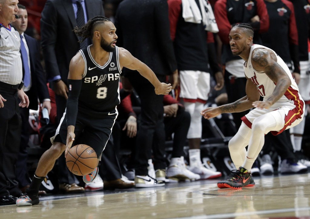San Antonio Spurs guard Patty Mills (8) controls the ball as Miami Heat forward Rodney McGruder defends during the first half of an NBA basketball gam...