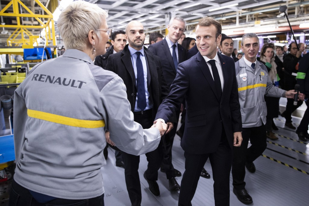 French President Emmanuel Macron shakes hands to workers as he visits the Renault factory in Maubeuge northern France, Thursday Nov. 8 2018. Macron is...