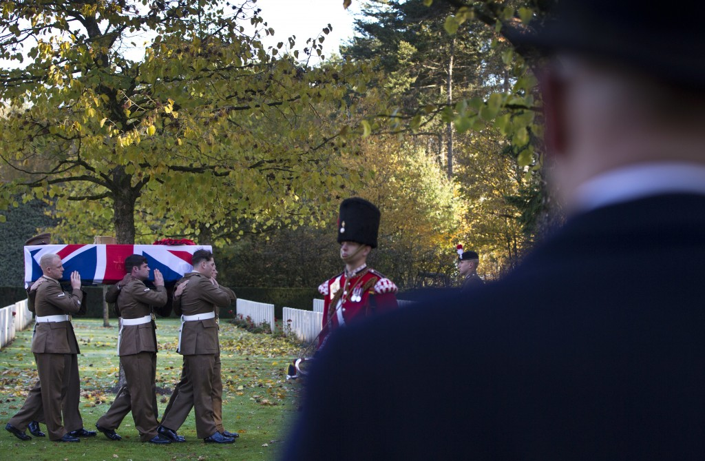British soldiers carry the coffin of an unknown British World War I soldier during a reburial ceremony at Buttes New British cemetery in Zonnebeke, Be