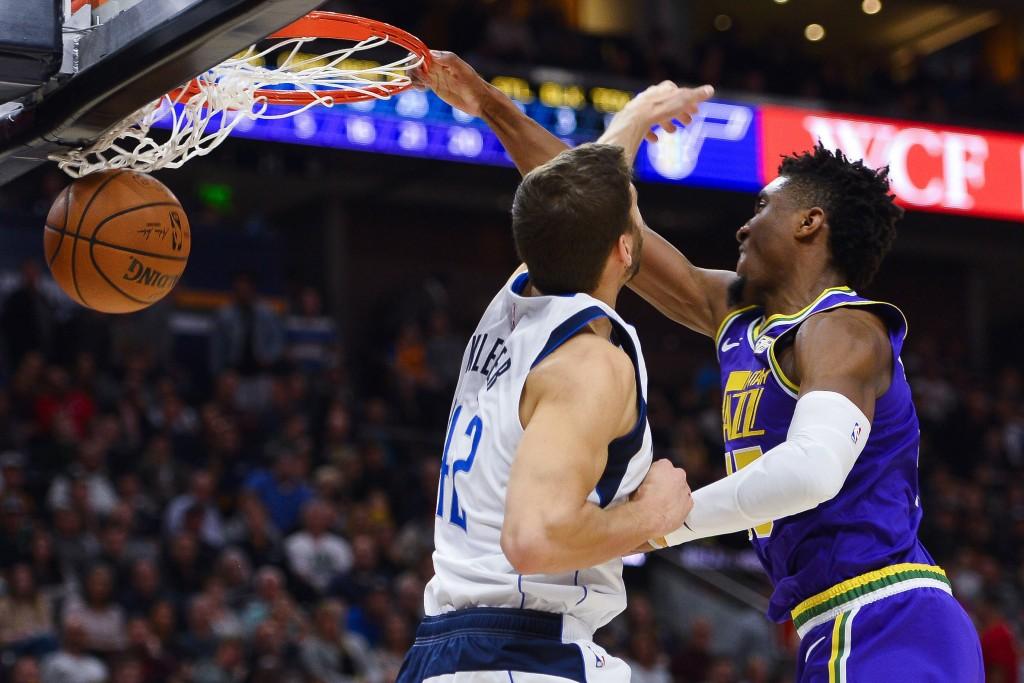 Utah Jazz guard Donovan Mitchell (45) dunks over Dallas Mavericks forward Maximilian Kleber (42) during the first half of an NBA basketball game Wedne