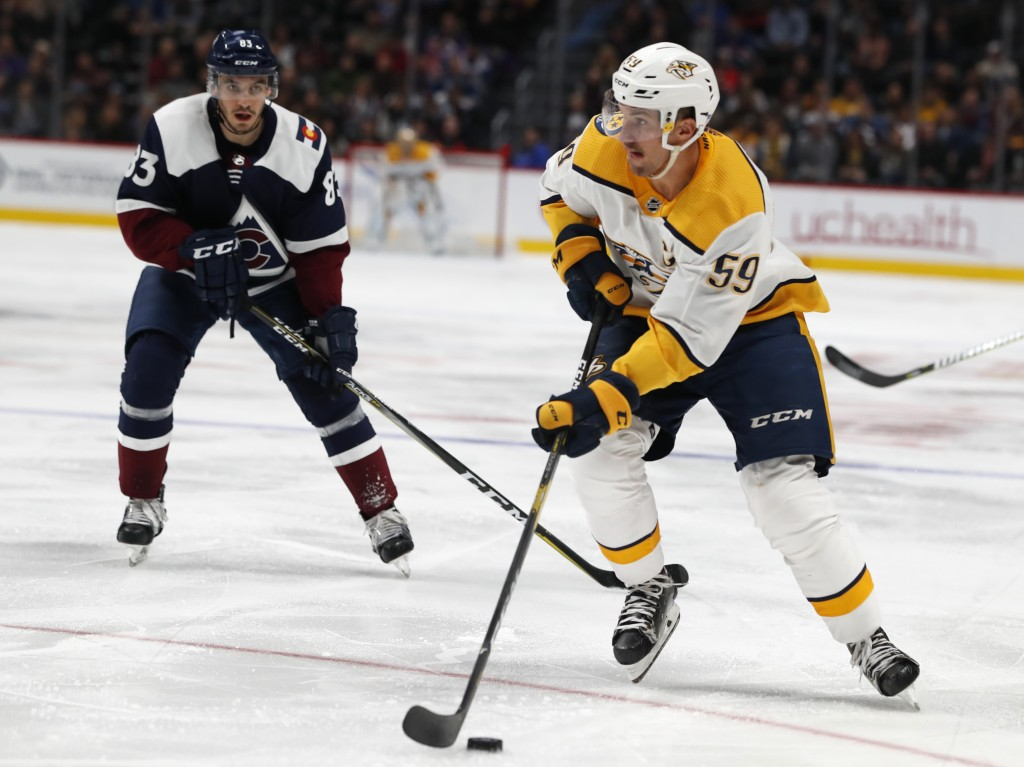 Nashville Predators defenseman Roman Josi, front, drives to the net past Colorado Avalanche left wing Matt Nieto during the second period of an NHL ho