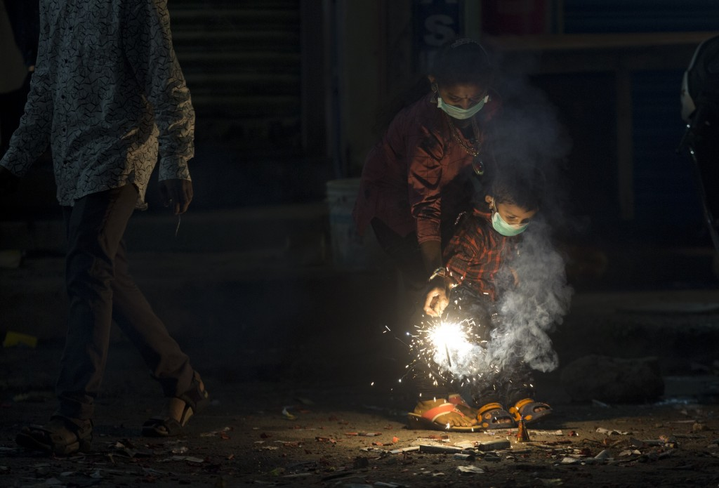 Indians light fire crackers wearing masks to fight pollution as they celebrate Diwali, the festival of lights in Hyderabad, India, Wednesday, Nov. 7,