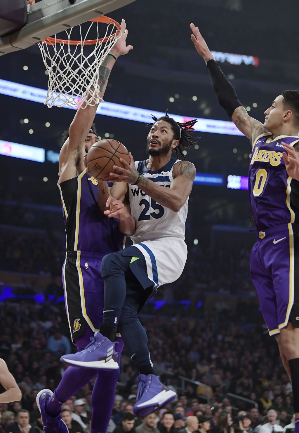 Minnesota Timberwolves guard Derrick Rose, center, goes to the basket as Los Angeles Lakers center JaVale McGee, left, and forward Kyle Kuzma defend d
