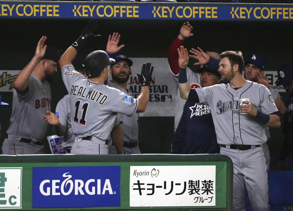 MLB All-Star's J.T. Realmuto (11) of the Miami Marlins is celebrated by teammates after hitting a solo home-run off Yomiuri Giants pitcher Ryusei Oe i...