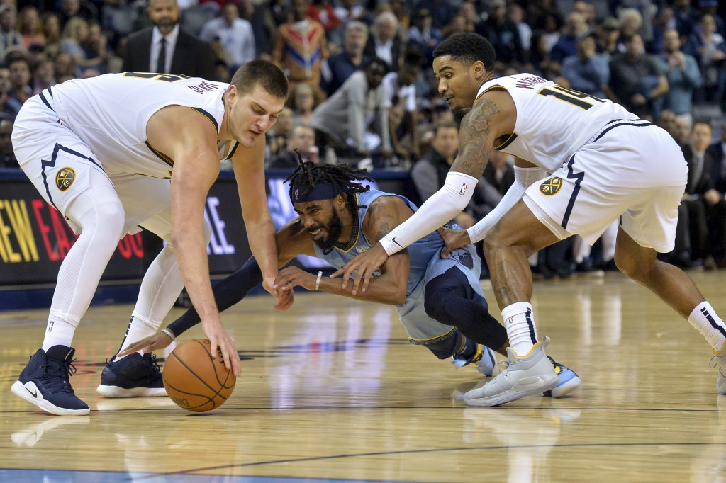 Memphis Grizzlies guard Mike Conley, center, dives for the ball between Denver Nuggets center Nikola Jokic, left, and guard Gary Harris in the second ...