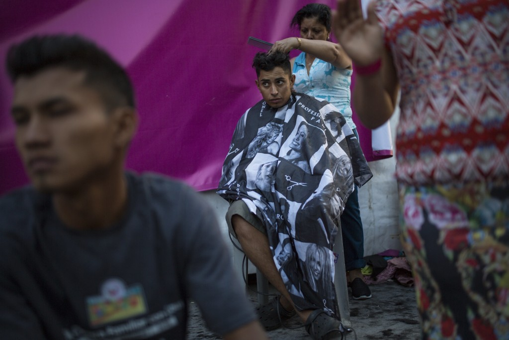 Honduran migrant Luis Fernando Barahona looks at an ongoing catholic mass while a hairdresser cuts his hair at a shelter at the Jesus Martinez stadium