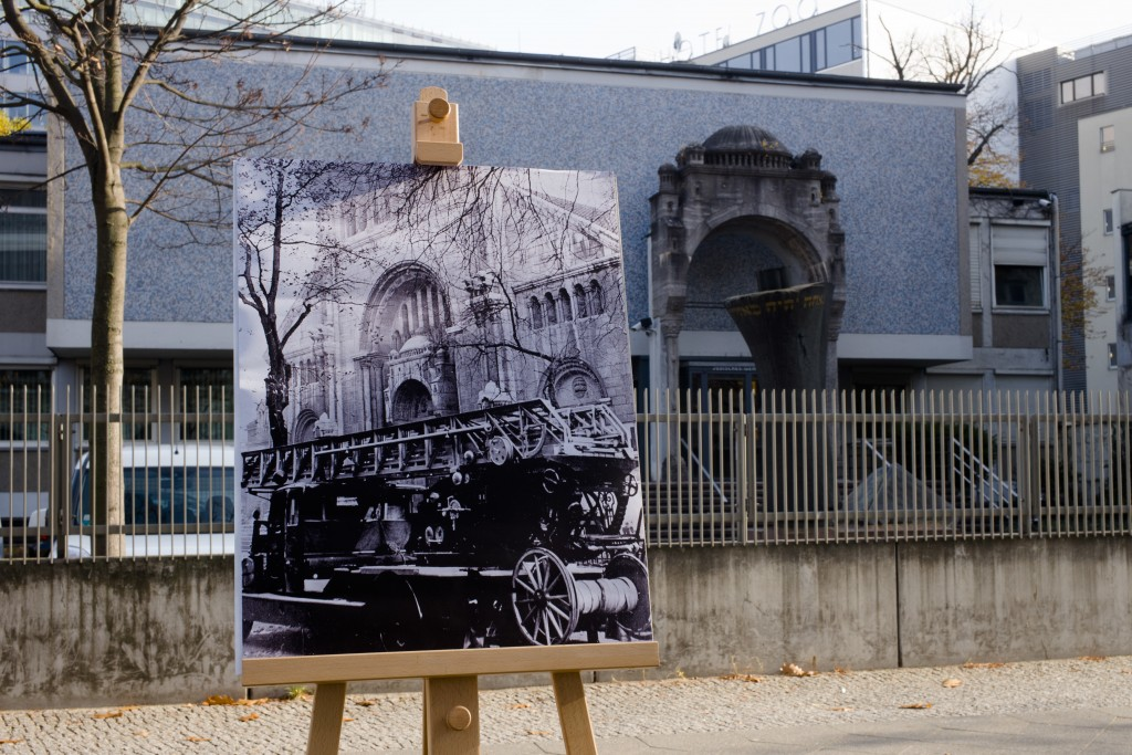 In this Wednesday, Nov. 7, 2018 photo a Nov. 10, 1938 photo from the AP Archive, showing a fire engine outside the Jewish synagogue on Fasanenstrasse ...