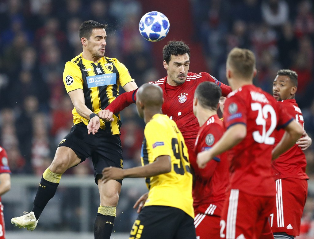 Bayern defender Mats Hummels, center, and AEK's Vasileios Lampropoulos jump for the ball during the Champions League group E soccer match between FC B