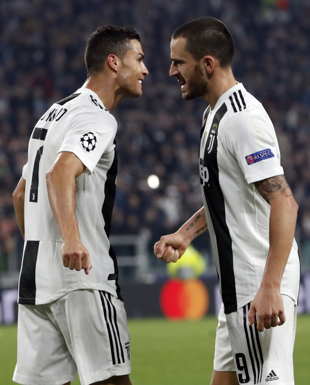Juventus forward Cristiano Ronaldo celebrates with teammate Leonardo Bonucci, right, after scoring his side's opening goal during the Champions League