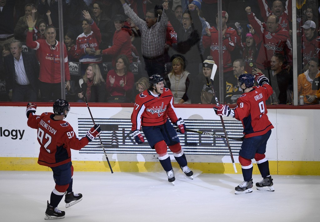 Washington Capitals right wing T.J. Oshie (77) celebrates his goal with center Evgeny Kuznetsov (92), of Russia, and defenseman Dmitry Orlov (9), of R...