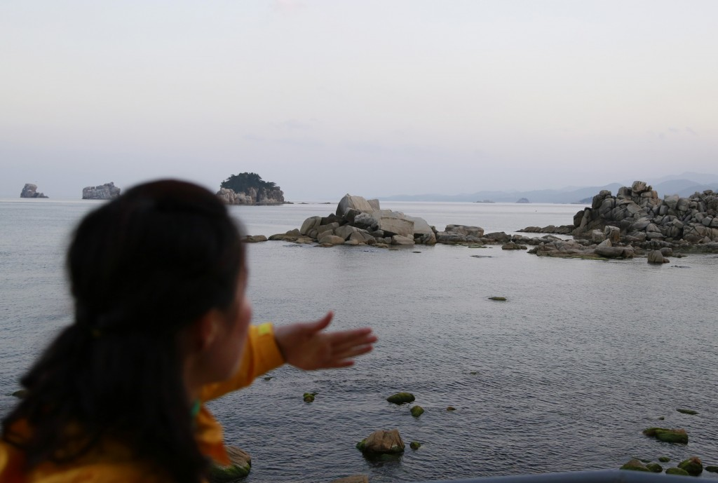 In this Oct. 23, 2018, photo, a tour guide gestures as she explains about a beach where people can see South Korea on the distant horizon at the Mount