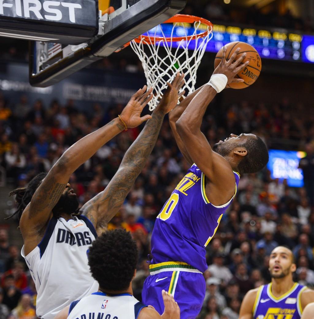 Utah Jazz guard Alec Burks (10) shoots over Dallas Mavericks center DeAndre Jordan, left, during the first half of an NBA basketball game Wednesday, N