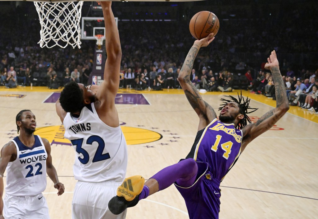 Los Angeles Lakers forward Brandon Ingram, right, shoots as Minnesota Timberwolves center Karl-Anthony Towns, center, defends and forward Andrew Wiggi