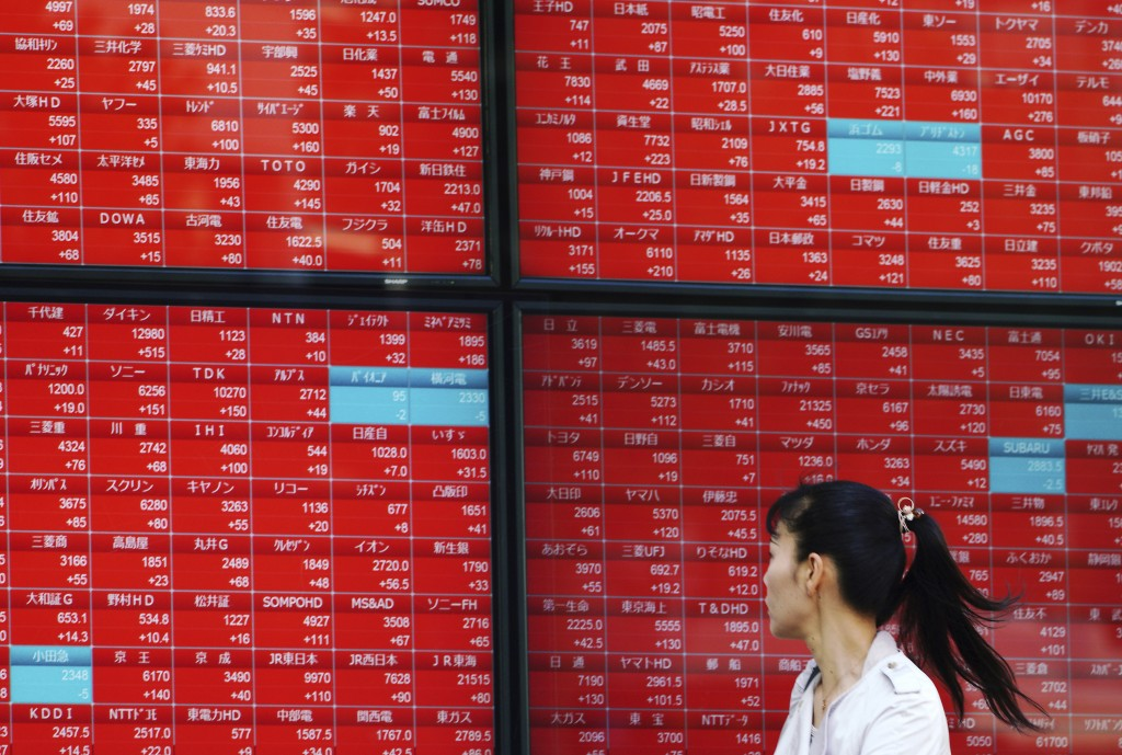 A woman walks past as she looks at an electronic stock board showing Japan's Nikkei 225 index at a securities firm in Tokyo Thursday, Nov. 8, 2018. As