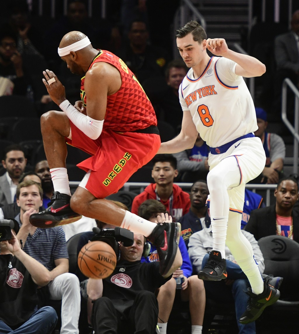 Atlanta Hawks forward Vince Carter and New York Knicks forward Mario Hezonja (8) vie for a loose ball during the first half of an NBA basketball game