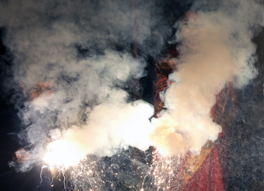 Seen through firework smoke, people celebrate Diwali in Allahabad, India, Wednesday, Nov. 7, 2018. Diwali, the festival of lights, is one of Hinduism'