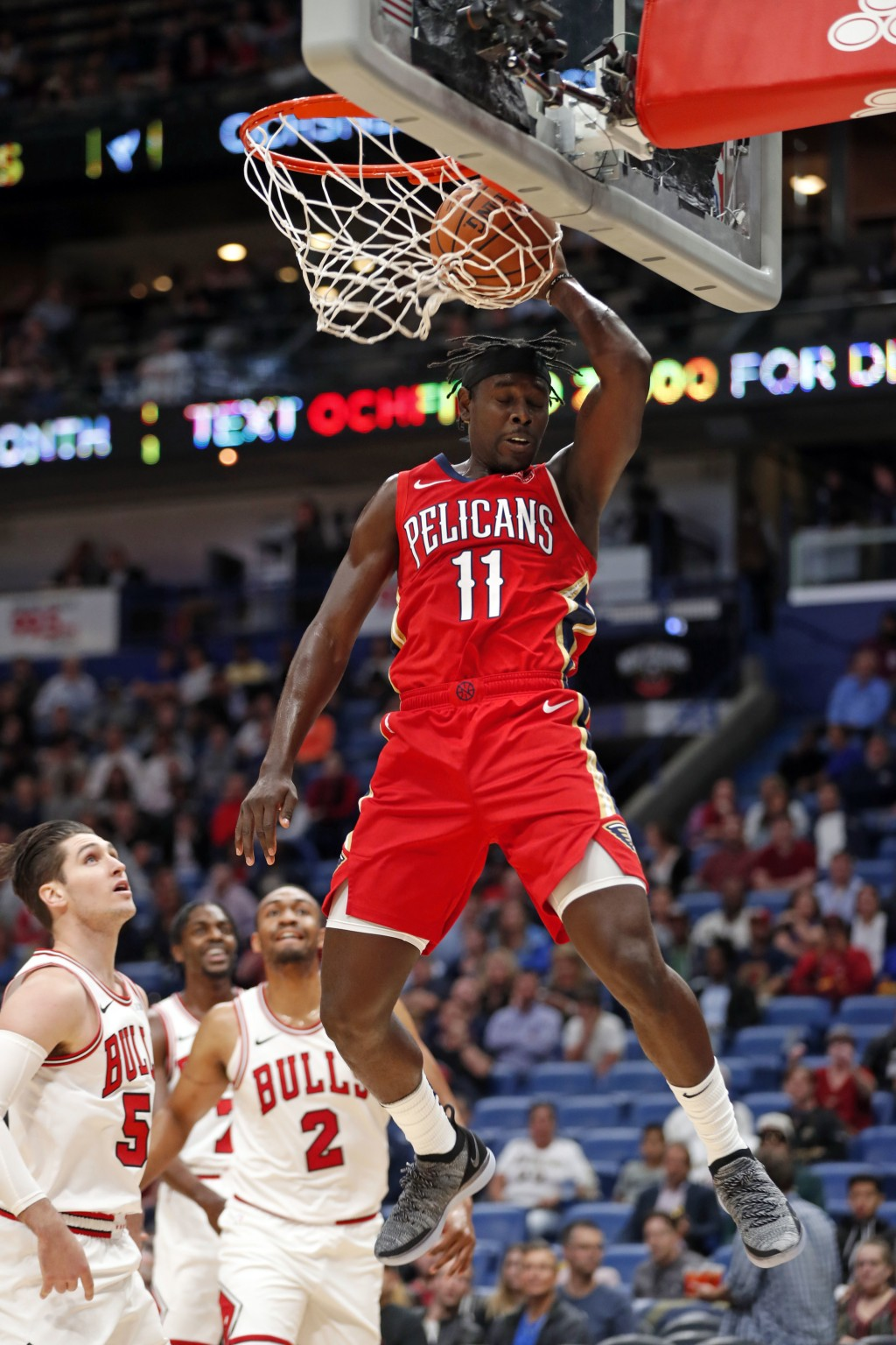 New Orleans Pelicans guard Jrue Holiday (11) dunks over Chicago Bulls forwards Bobby Portis (5) and Jabari Parker (2) during the first half of an NBA